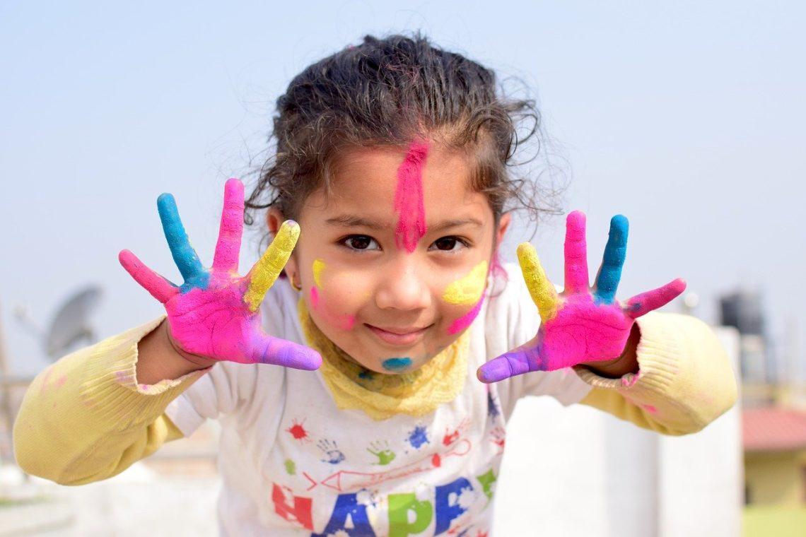 Knutselen met een peuter: meisje met geschilderde handen en hoofd.