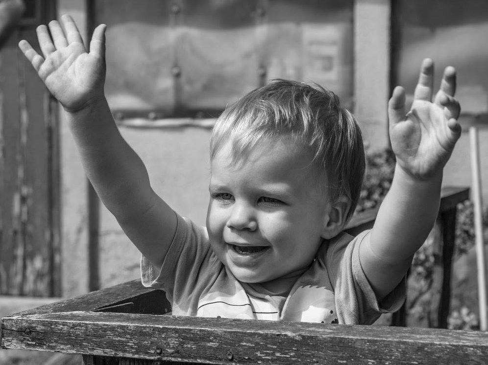 Positief opvoeden: foto van vrolijke peuter die zijn handjes in de lucht steekt