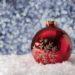 Stress tijdens de feestdagen voorkomen: foto van een kerstbal in de sneeuw.
