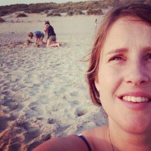 Selfie met 3 spelende kinderen op het strand