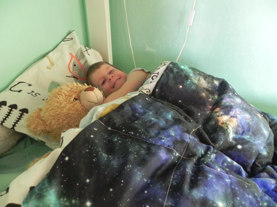 Verzwaringsdeken voor een kind: kleuter ligt in bed met een verzwaringsdeken.