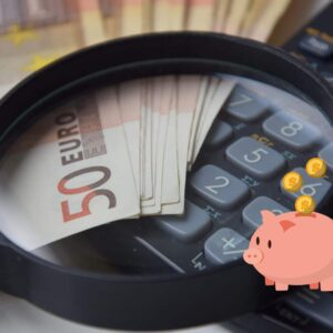 Geld besparen tijdens corona: foto van een rekenmachine met 50 euro briefjes en een loep.
