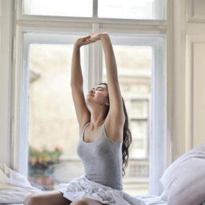 Je week goed beginnen: foto van een vrouw die op bed zit en zich uitrekt.